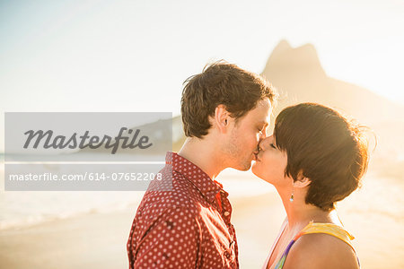 Young couple kissing at sunset, Ipanema Beach, Rio, Brazil Stock Photo - Premium Royalty-Free, Image code: 614-07652208