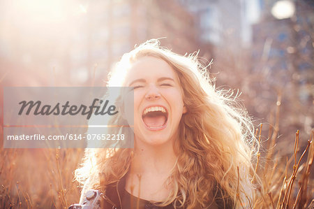 Young woman in long grass with open mouth Stock Photo - Premium Royalty-Free, Image code: 614-07652218