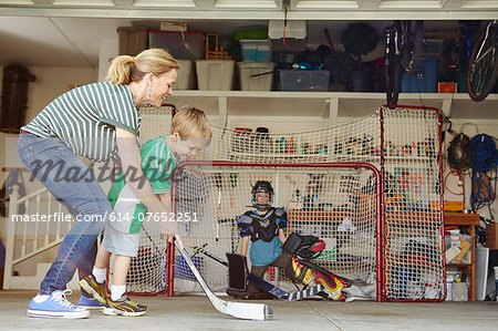 Mother playing hockey in garage with two sons Stock Photo - Premium Royalty-Free, Image code: 614-07652251