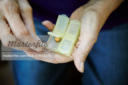 Close up of 82 year old senior woman's hand with pill box Stock Photo - Premium Royalty-Free, Image code: 614-07652270
