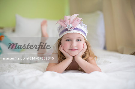 Portrait of young girl in princess headdress on bed Stock Photo - Premium Royalty-Free, Image code: 614-07652345
