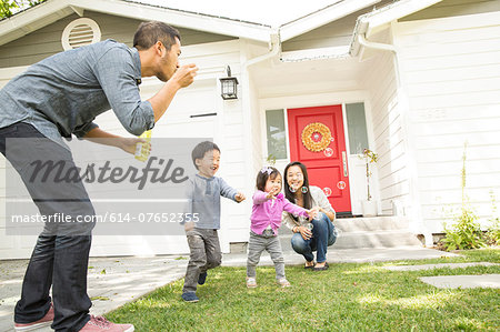 Mid adult couple with two children blowing bubbles Stock Photo - Premium Royalty-Free, Image code: 614-07652355