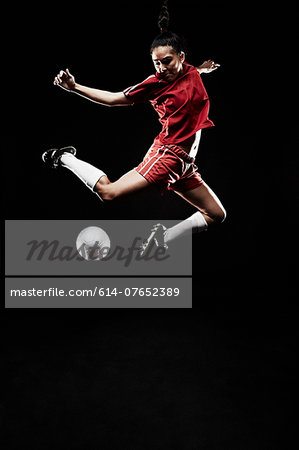 Young woman jumping for football Stock Photo - Premium Royalty-Free, Image code: 614-07652389