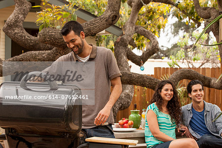 Man cooking on barbecue, friends in background Stock Photo - Premium Royalty-Free, Image code: 614-07652461