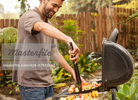 Man cooking vegetable skewers on barbecue Stock Photo - Premium Royalty-Free, Image code: 614-07652463