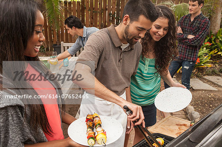 Friends sitting around table sharing barbecue food Stock Photo - Premium Royalty-Free, Image code: 614-07652465