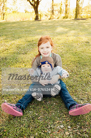Portrait of girl and baby brother on grass in park Stock Photo - Premium Royalty-Free, Image code: 614-07652494