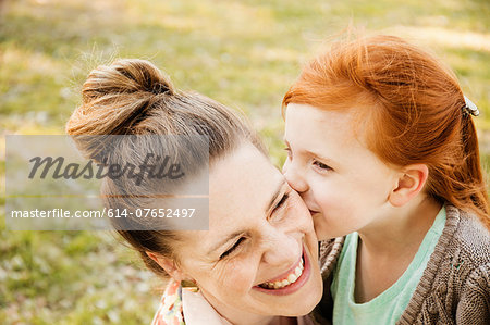 Portrait of smiling mid adult mother and daughter in park