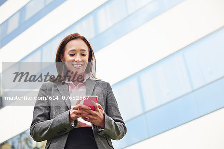 Young female businesswoman texting on smartphone outside office Stock Photo - Premium Royalty-Free, Image code: 614-07652567
