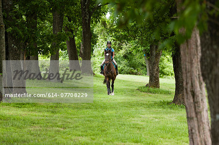 Young woman riding horse through forest Stock Photo - Premium Royalty-Free, Image code: 614-07708229
