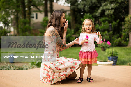 Mother and toddler daughter blowing bubbles in garden Stock Photo - Premium Royalty-Free, Image code: 614-07708340
