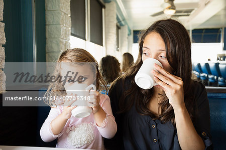 Mother and toddler drinking mugs of coffee in diner Stock Photo - Premium Royalty-Free, Image code: 614-07708348