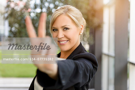 Portrait of young businesswoman making victory sign Stock Photo - Premium Royalty-Free, Image code: 614-07735182