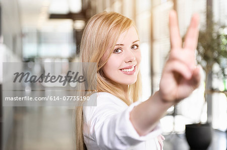 Portrait of confident young businesswoman making victory sign with hand Stock Photo - Premium Royalty-Free, Image code: 614-07735190