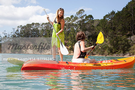 Senior woman and daughter playfighting from kayak and paddleboard Stock Photo - Premium Royalty-Free, Image code: 614-07735240