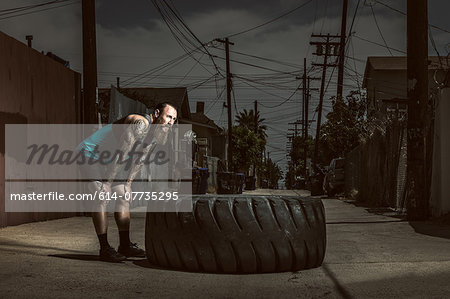 Mid adult man standing by large tire Stock Photo - Premium Royalty-Free, Image code: 614-07735295