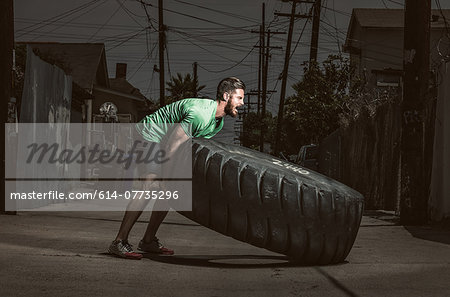 Young adult man lifting large tire, crossfit exercise Stock Photo - Premium Royalty-Free, Image code: 614-07735296
