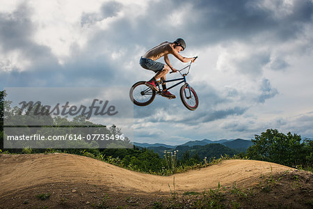 Young man doing BMX trick on rural pump track Stock Photo - Premium Royalty-Free, Image code: 614-07735496
