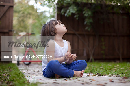 Four year old girl sitting on garden path gazing upward Stock Photo - Premium Royalty-Free, Image code: 614-07735500