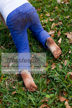 Four year old girl waist down crawling on garden grass Stock Photo - Premium Royalty-Free, Image code: 614-07735502
