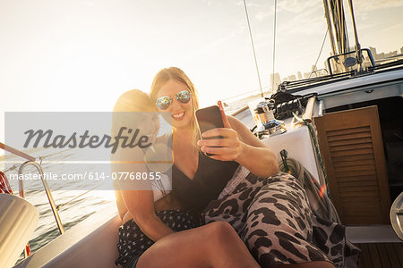 Two women on yacht using smartphone Stock Photo - Premium Royalty-Free, Image code: 614-07768055