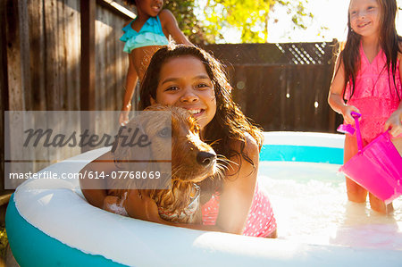 Three girls and a dog in garden paddling pool Stock Photo - Premium Royalty-Free, Image code: 614-07768069