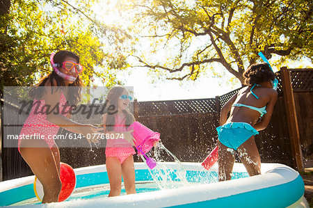 Three girls playing and splashing in garden paddling pool Stock Photo - Premium Royalty-Free, Image code: 614-07768074