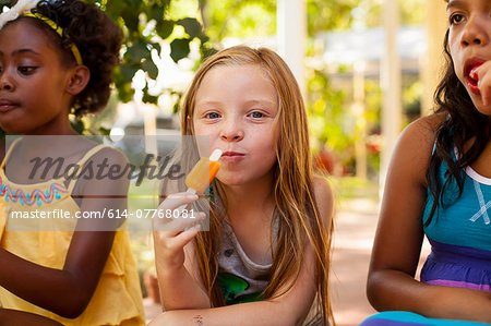 Portrait of three girls eating ice lollies in garden Stock Photo - Premium Royalty-Free, Image code: 614-07768081