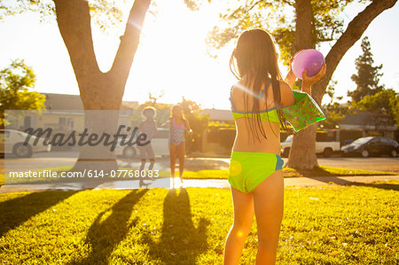 Girl chasing friends with water balloon in garden Stock Photo - Premium Royalty-Free, Image code: 614-07768083