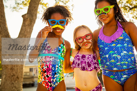 Portrait of girls in spectacles and mustaches in garden Stock Photo - Premium Royalty-Free, Image code: 614-07768087