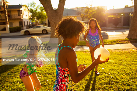 Three girls playing with water balloons in garden