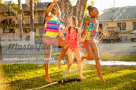 Three girls running and jumping in garden sprinkler Stock Photo - Premium Royalty-Free, Image code: 614-07768093