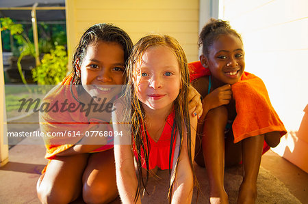 Portrait of three girls wrapped in towel on porch Stock Photo - Premium Royalty-Free, Image code: 614-07768094