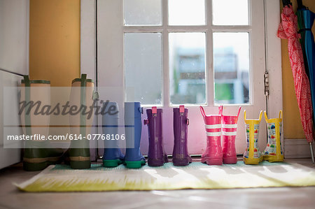 Tidy row of rubber boots at back door Stock Photo - Premium Royalty-Free, Image code: 614-07768106