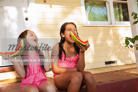 Two laughing girls sitting on house porch with slices of watermelon Stock Photo - Premium Royalty-Free, Image code: 614-07768115