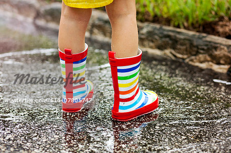 Legs of girl wearing rubber boots standing in rain puddle Stock Photo - Premium Royalty-Free, Image code: 614-07805747