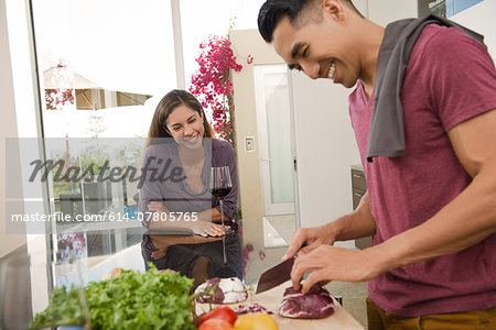 Couple chatting and chopping vegetables in kitchen Stock Photo - Premium Royalty-Free, Image code: 614-07805765
