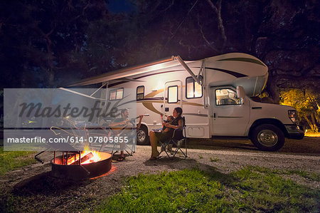 Mid adult couple and baby daughter sitting in front of campfire at night Stock Photo - Premium Royalty-Free, Image code: 614-07805855
