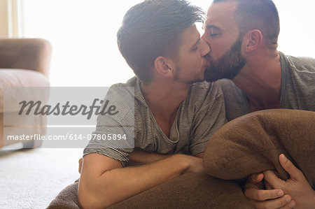 Male couple kissing on sitting room sofa Stock Photo - Premium Royalty-Free, Image code: 614-07805894