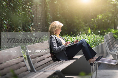Mature businesswoman sitting on bench using laptop Stock Photo - Premium Royalty-Free, Image code: 614-07805967