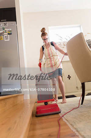 Young woman vacuuming with green cleaning products Stock Photo - Premium Royalty-Free, Image code: 614-07806108
