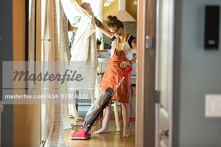 Young woman vacuuming with green cleaning products Stock Photo - Premium Royalty-Free, Image code: 614-07806122