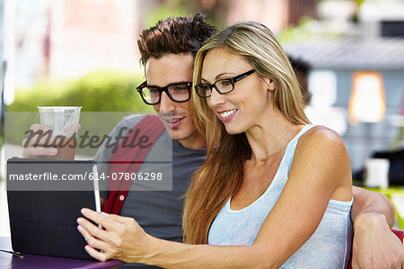 Couple using digital tablet at cafe Stock Photo - Premium Royalty-Free, Image code: 614-07806298