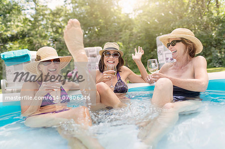 Three mature women sitting in paddling pool, drinking wine Stock Photo - Premium Royalty-Free, Image code: 614-07806346