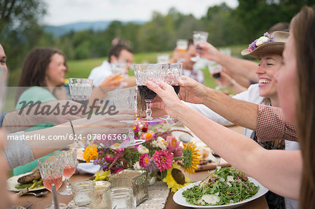 Family and friends making a toast at outdoor meal Stock Photo - Premium Royalty-Free, Image code: 614-07806369
