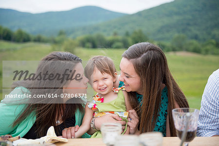 Baby girl sitting between two young women Stock Photo - Premium Royalty-Free, Image code: 614-07806371