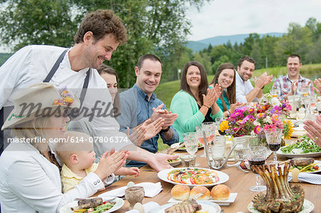 Mid adult man in apron, serving plate of food to family members at table, outdoors Stock Photo - Premium Royalty-Free, Image code: 614-07806374