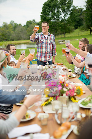 Family and friends making a toast at outdoor meal Stock Photo - Premium Royalty-Free, Image code: 614-07806389