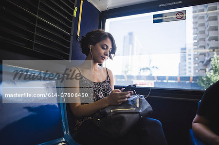 Young woman commuting on bus listening to music on smartphone, New York, US Stock Photo - Premium Royalty-Free, Image code: 614-07806450