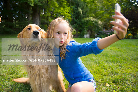 Girl taking selfie with pet dog in garden